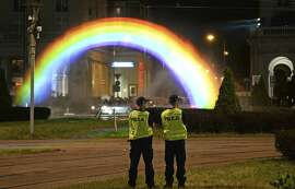 Police officers stand next to a light and water rainbow installation on the night before a gay pride parade, in downtown Warsaw, Poland, Friday, June 8, 2018. (AP Photo/Alik Keplicz)
