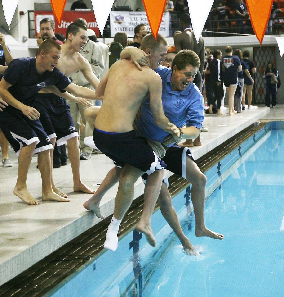2/28/09 -- Humble Kingwood swimmers push head coach Russell Duin into the pool after winning the Boys' team standings at the UIL 5A Swimming State Championships at the Jamail Texas Swimming Center in Austin, Texas. Saturday, February 28, 2009 -- THE DALLAS MORNING NEWS
