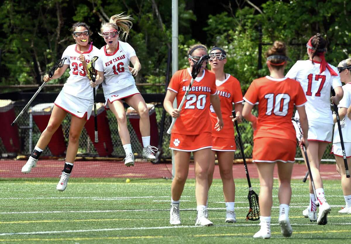 Karlie Bucci (left) and Braeden Dial of New Canaan celebrate after scoring in the second half of New Canaan's 19-7 victory over Ridgefield in the CIAC Class L Girls Lacrosse Finals at Jonathan Law High School in Milford on June 9, 2018.
