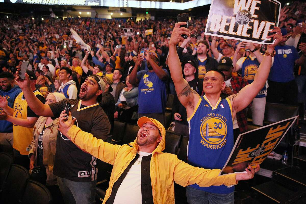 From left: Rudy Balderramos, Rodel Calipes and Rommel Sigua cheer at the end of the game during a Golden State Warriors watch party at Oracle Arena, Friday, June 8, 2018, in Oakland, Calif. Visitors watched on the jumbotron Game 4 of the NBA Finals between the Warriors and Cleveland Cavaliers.