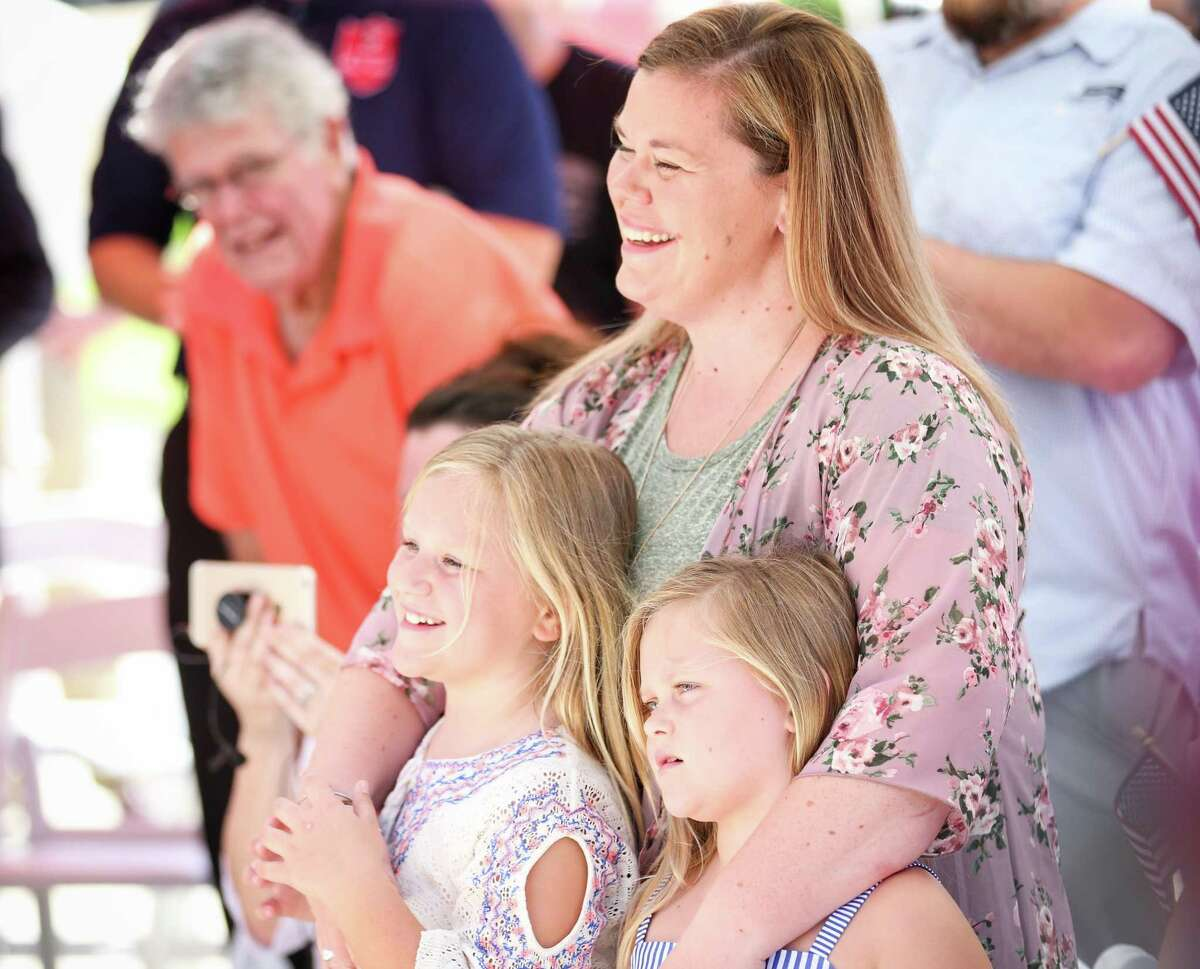 Erin Kadleck laughs while hugging two of her children during the Operation Finally Home house unveiling on Friday, June 8, 2018, in The Woodlands.