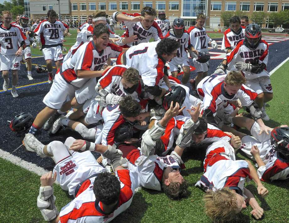 New Fairfield High School players run from the bench and pile on goalkeeper Brennan Hart (20) after winning the boys lacrosse Class M State Championship by defeating Daniel Hand 13 to 11. Saturday, June 9, 2018, at Brien McMahon High School, Norwalk, Conn. Photo: H John Voorhees III / Hearst Connecticut Media / The News-Times