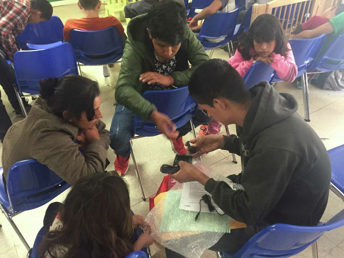 Migrants show Santiago Choc Chomo, a Guatemalan father who was briefly separated from his 10-year-old daughter, how to charge his electronic ankle monitoring bracelet. He was released and rejoined with the girl because immigration officials had no more space to hold him.