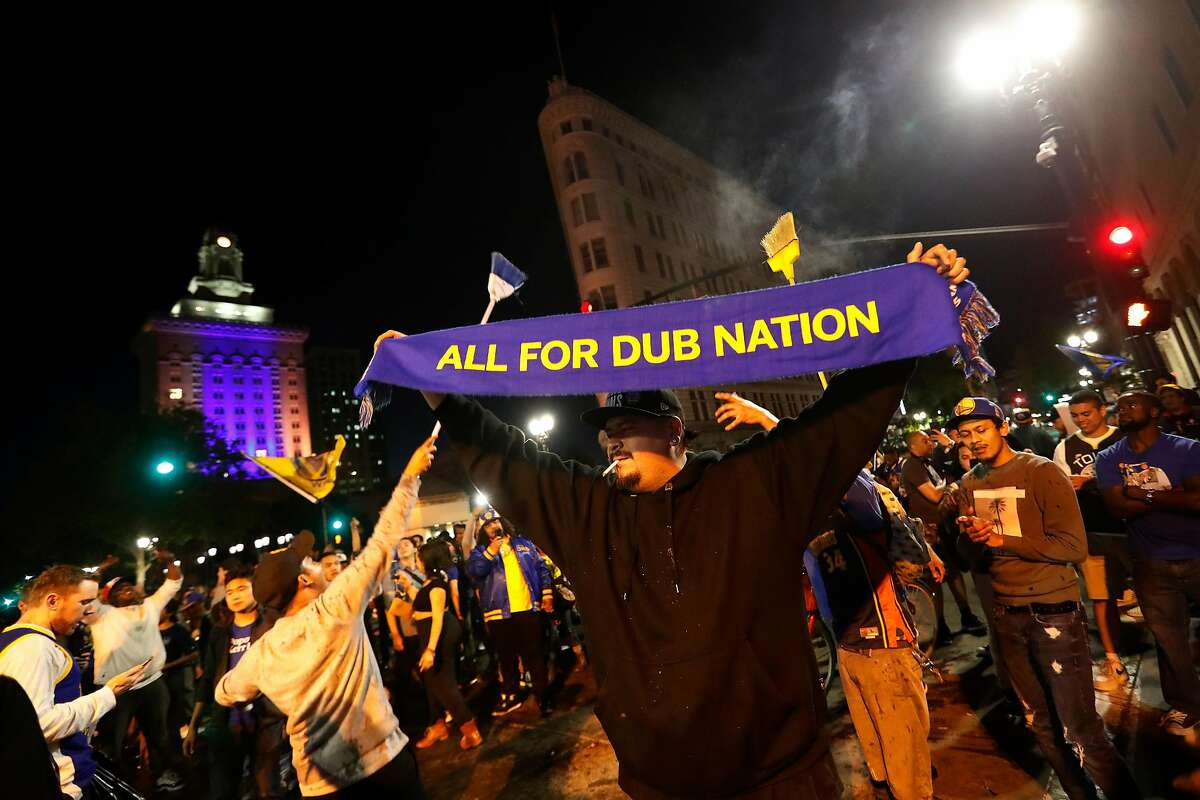 Basketball fans celebrate on 14th and Broadway after the Golden State Warriors defeated the Cleveland Cavaliers 108-85 in Game 4 to win the NBA Finals in Oakland, Calif. on Friday, June 8, 2018.