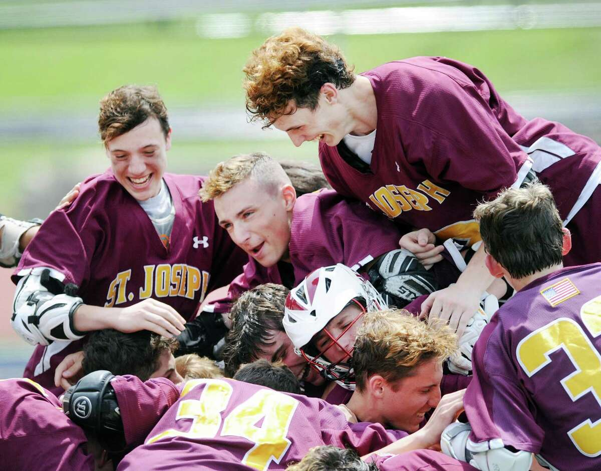 St. Joe's players mob their goalie Kyle Burbank (bottom of pile) at the conclusion of St. Joe's 11-6 victory over Somers in the boys high school lacrosse Class S title game at Brien McMahon High School in Norwalk, Conn., Saturday, June 9, 2018.
