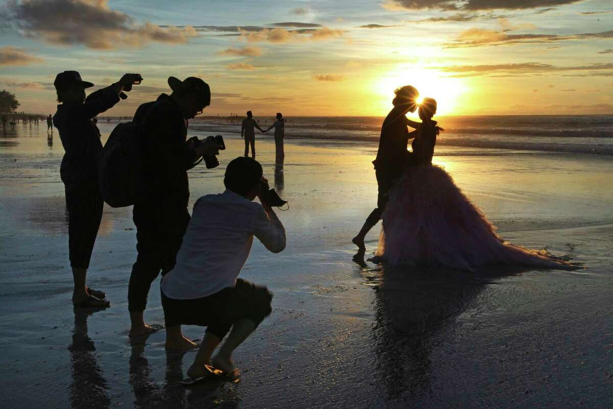 In this Jan. 18, 2017, file photo, photographers take photos of a tourist couple's wedding at the famous Kuta beach during sunset in Bali, Indonesia. According to a 2016 survey from wedding site The Knot, the average cost of an international destination wedding is $25,800. That figure may be within your event budget, but for guests, international airfare and multinight lodging could be out of reach. (AP Photo/Firdia Lisnawati, File)
