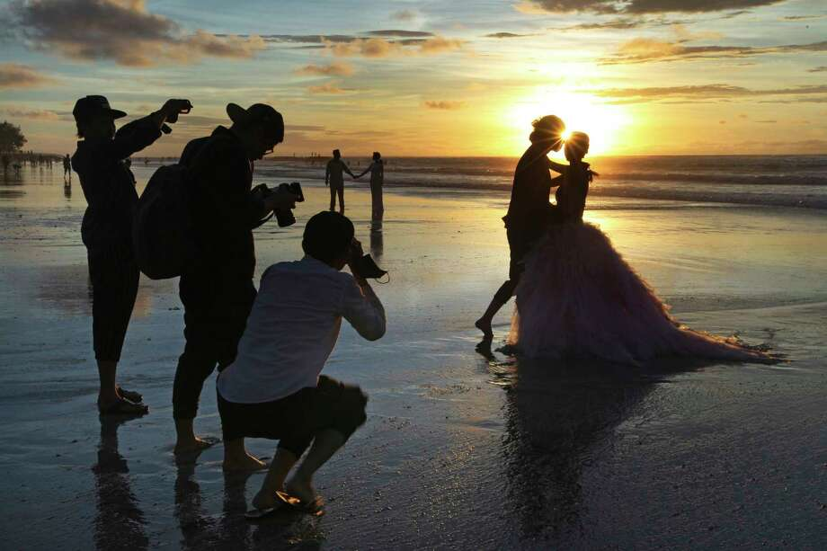 FILE- In this Jan. 18, 2017, file photo, photographers take photos of a tourist couple's wedding at the famous Kuta beach during sunset in Bali, Indonesia. According to a 2016 survey from wedding site The Knot, the average cost of an international destination wedding is $25,800. That figure may be within your event budget, but for guests, international airfare and multinight lodging could be out of reach. (AP Photo/Firdia Lisnawati, File) Photo: Firdia Lisnawati / Copyright 2017 The Associated Press. All rights reserved.