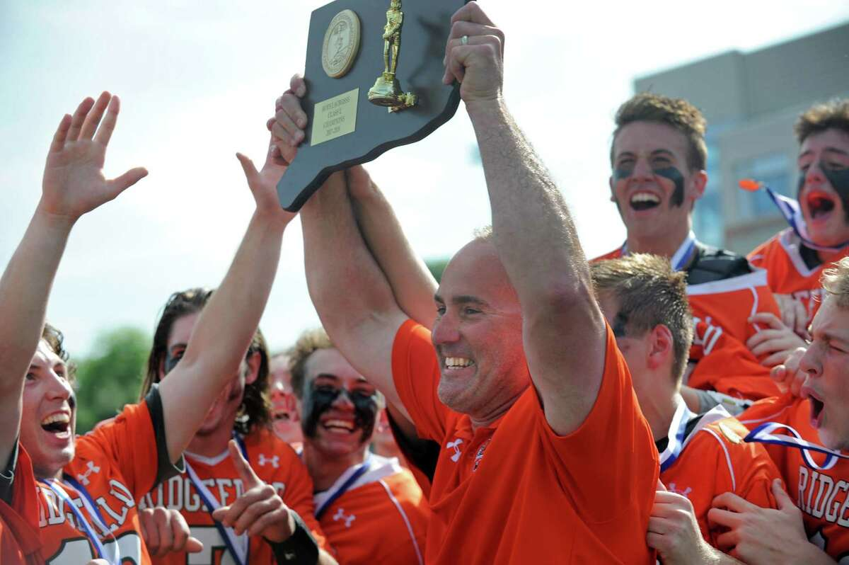 Ridgefield High School Boys Lacrosse head coach Roy Colsey celebrates with his team after beating Darien in the Boys Lacrosse-L State Championship Saturday, June 9, 2018, at Brien McMahon High School in Norwalk, Conn.