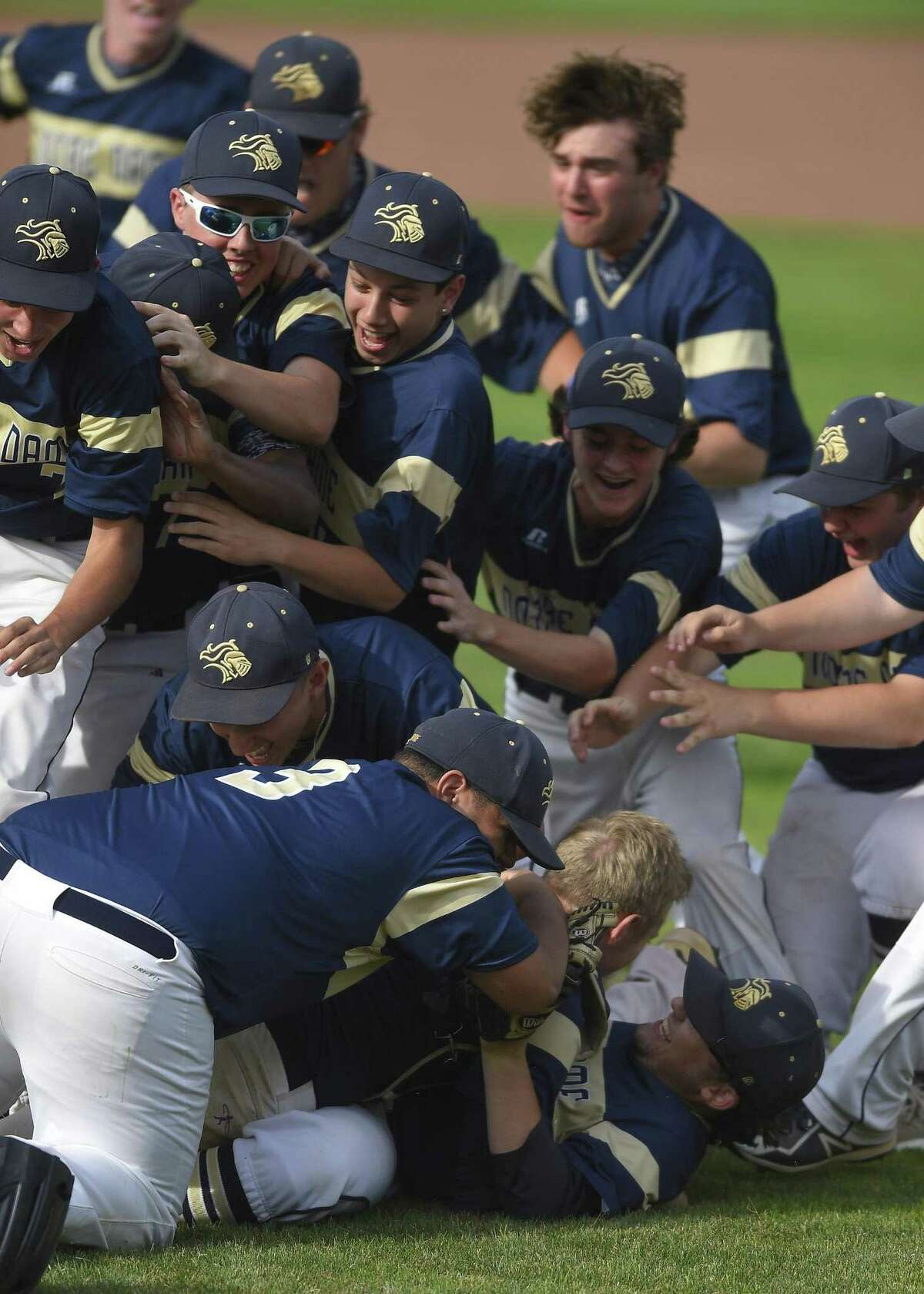 Notre Dame-Fairfield players pile onto pitcher Dillon Higgins after the Lancers defeated Coventry 10-6 to win the Class S title on Saturday at Palmer Field in Middletown.
