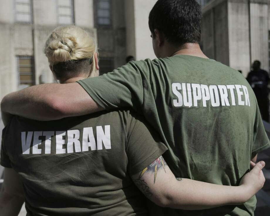 Army veteran Justine Phillips, puts her arm around Chad Henderson as they listen to Rep. Al Green during a women veteran's march at Houston City Hall on Saturday, June 9, 2018 in Houston. The veterans marched to celebrate progress and speak out for against abuse and challenges they face. (Elizabeth Conley/Houston Chronicle) Photo: Elizabeth Conley, Chronicle / Houston Chronicle / ©2018 Houston Chronicle