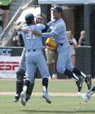North Carolina pitcher Josh Hiatt (31) hugs catcher Brandon Martorano as infielder Dallas Tessar (7) celebrates following the team's win over Stetson following an NCAA super regional college baseball game in Chapel Hill, N.C., Saturday, June 9, 2018. North Carolina won 7-5 to advance to the College World Series. (AP Photo/Gerry Broome)
