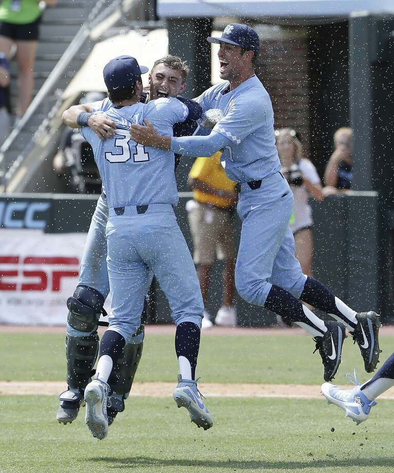 North Carolina pitcher Josh Hiatt (31) hugs catcher Brandon Martorano as infielder Dallas Tessar joins the celebration. Photo: Gerry Broome / Associated Press