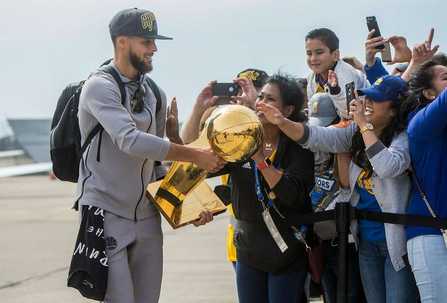 The Golden State Warriors' Stephen Curry lets fans touch the NBA Championship trophy after he arrives from Cleveland, Ohio at Landmark Aviation in Oakland, Calif. Saturday, June 9, 2018. after defeating the Cleveland Cavaliers in the NBA Finals. Photo: Jessica Christian / The Chronicle
