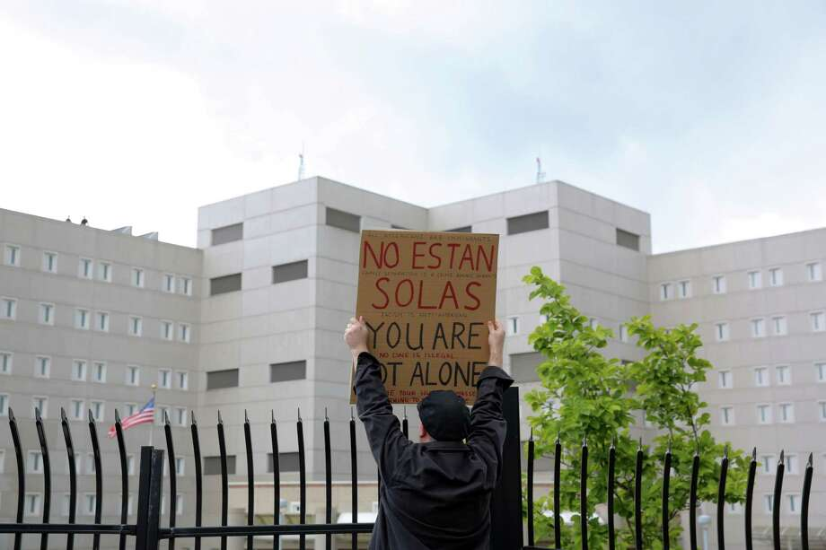 "Peter Smalley holds a sign reading ""You are not alone"" in both English and Spanish as he and several hundred protesters and elected officials including Washington State Governor Jay Inslee, State Attorney General Bob Ferguson and U.S. Rep. Pramila Jayapal (D-Seattle), gather at the Federal Detention Center in SeaTac where 174 women are being held, most of whom fled Central America to seek political asylum in the U.S., June 9, 2018.  According to Jayapal, who met with the women Saturday, many said their children were taken from them after they crossed the border into Texas. The protest included speeches, sign making, letter writing, and music. Photo: GENNA MARTIN, SEATTLEPI.COM / SEATTLEPI.COM"