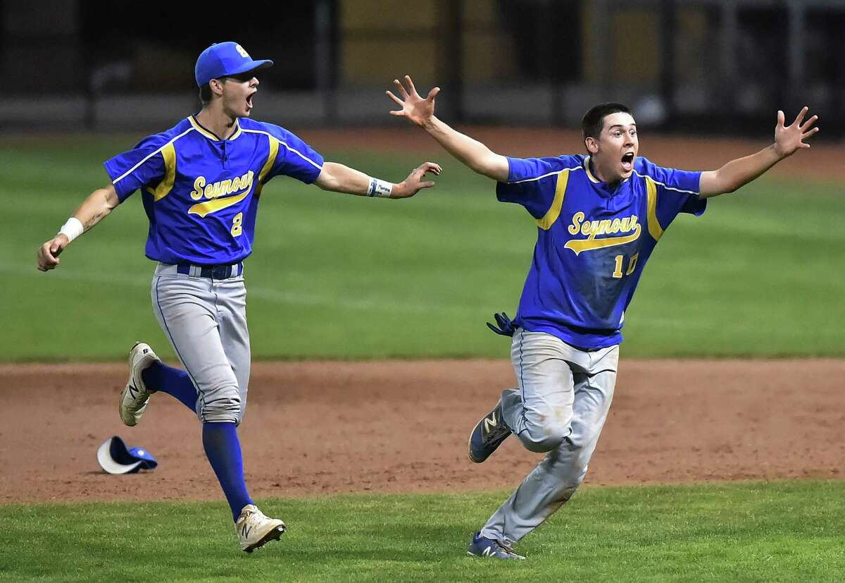Seymour senior Austin DeRosa (21) and Brandon Ellsworth (10) celebrate their championship 13-2 victory over Wolcott in the Class M title game on Saturday.