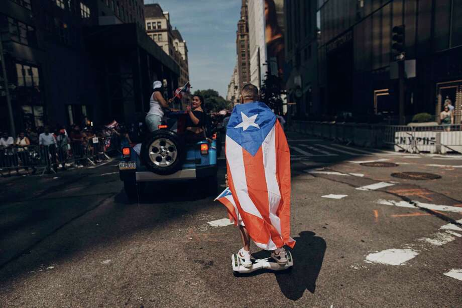 FILE - In this June 11, 2017 file photo, a man rolls on a hover-board along Fifth Avenue during the National Puerto Rican Day Parade in New York.  Amid all the fun and celebration planned for this years parade on Sunday, June 10, 2018, organizers and participants want to keep a spotlight on something serious. They want people to remember that months after Hurricane Maria roared through and as the next hurricane season arrives, Puerto Rico is still struggling. (AP Photo/Andres Kudacki) Photo: Andres Kudacki / FR170905 AP