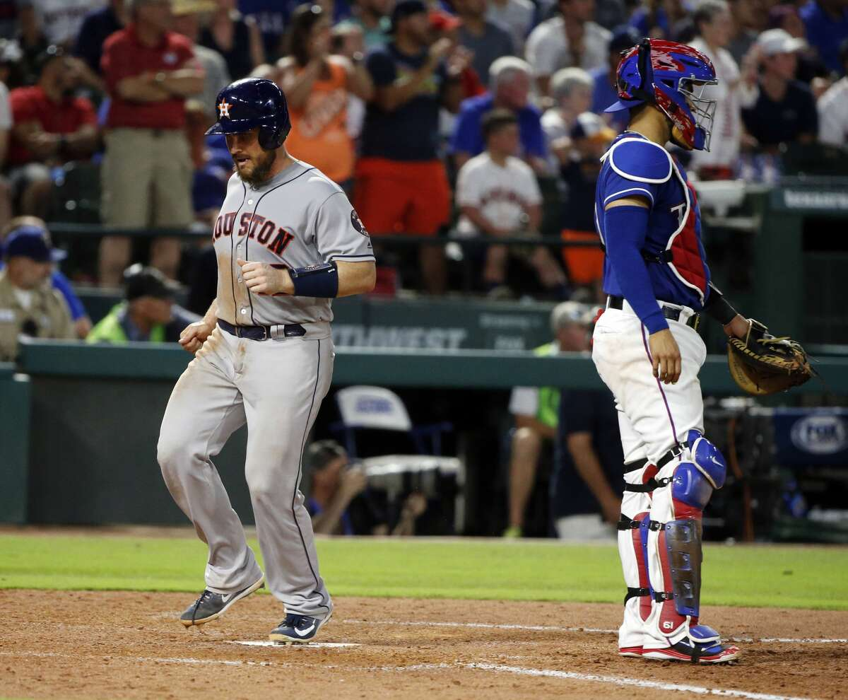 Houston Astros' Max Stassi (12) scores a run next to Texas Rangers catcher Robinson Chirinos (61) during the seventh inning of a baseball game Saturday, June 9, 2018, in Arlington, Texas. (AP Photo/Michael Ainsworth)