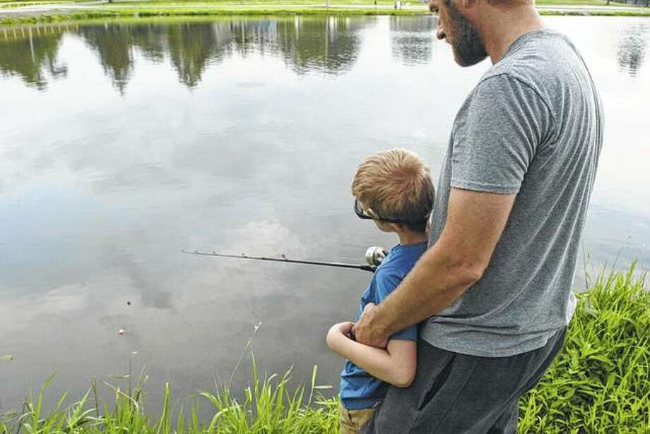 Averi Tacker, 10, and his father, Brian Tacker, of Riverton try their luck Saturday in the second annual Jacksonville Kiwanis Take Me Fishing event at Morgan Lake in Nichols Park. The event is designed for children ages 3 through 15 with learning or developmental disabilities. Photo:       Greg Olson | Journal-Courier