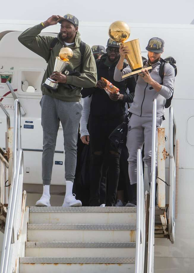 The Golden State Warriors' Stephen Curry carries the NBA Championship trophy while Warriors' Kevin Durant carries his MVP trophy as the team arrives from Cleveland, Ohio at Landmark Aviation in Oakland, Calif. Saturday, June 9, 2018. after defeating the Cleveland Cavaliers in the NBA Finals. Photo: Jessica Christian, The Chronicle