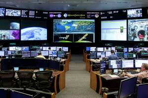 """Timothy """"T.J."""" Creamer, right, a former astronaut and current mission control flight director at N.A.S.A., works in the mission control room at the Johnson Space Center, Friday, April 27, 2018, in Houston."""