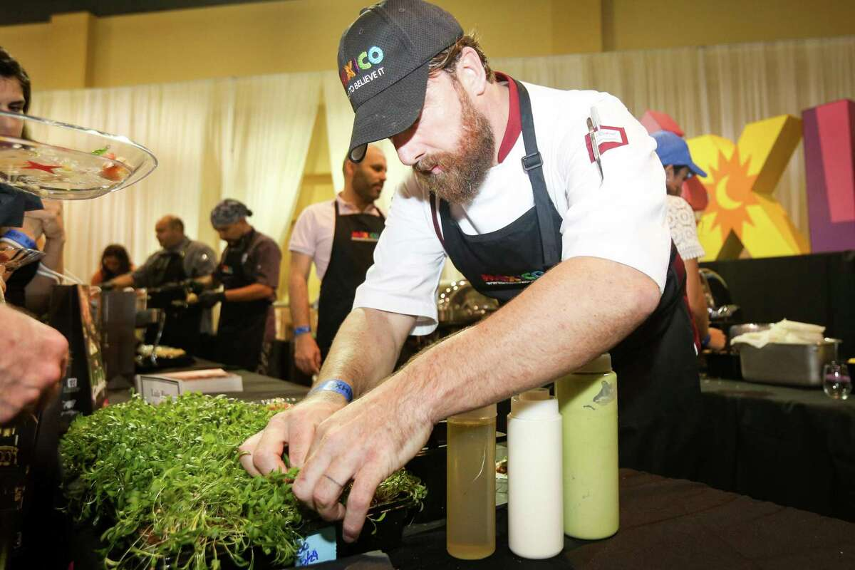 Darren Walsh, a chef from Guadalajara, Mexico, picks fresh cilantro for tacos during Sips, Suds & Tacos on Friday at the Woodlands Waterway Marriott Hotel and Convention Center.