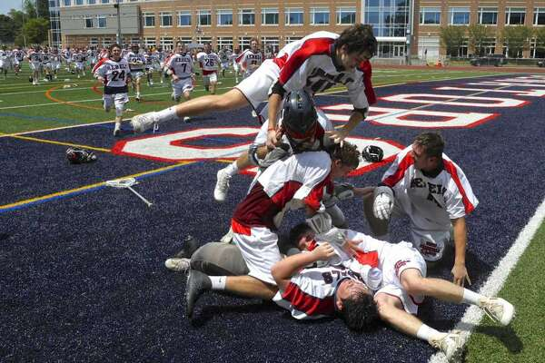 New Fairfield High School players run from the bench and pile on goalkeeper Brennan Hart (20) after winning the boys lacrosse Class M State Championship by defeating Daniel Hand 13 to 11. Saturday, June 9, 2018, at Brien McMahon High School, Norwalk, Conn