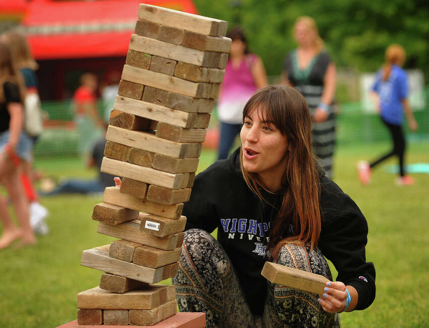 Nina Zovko, of Montclair, NJ, tries her hand at a game of Jenga at the Riverfront Music Festival in Shelton, Conn. on Sunday, June 10, 2018.