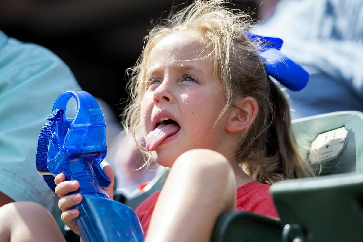 Texas Rangers fan Gianna Styles, 6, tries to cool off in the 97-degree heat during the sixth inning of a baseball game between the Texas Rangers and the Houston Astros, Sunday, June 10, 2018, in Arlington, Texas. (AP Photo/Jeffrey McWhorter)