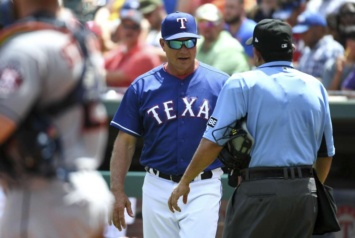 Texas Rangers manager Jeff Banister, center, argues with home plate umpire Alfonso Marquez about whether Rangers' Rougned Odor was hit by a pitch from Houston Astros starter Dallas Keuchel during the third inning of a baseball game, Sunday, June 10, 2018, in Arlington, Texas. (AP Photo/Jeffrey McWhorter)