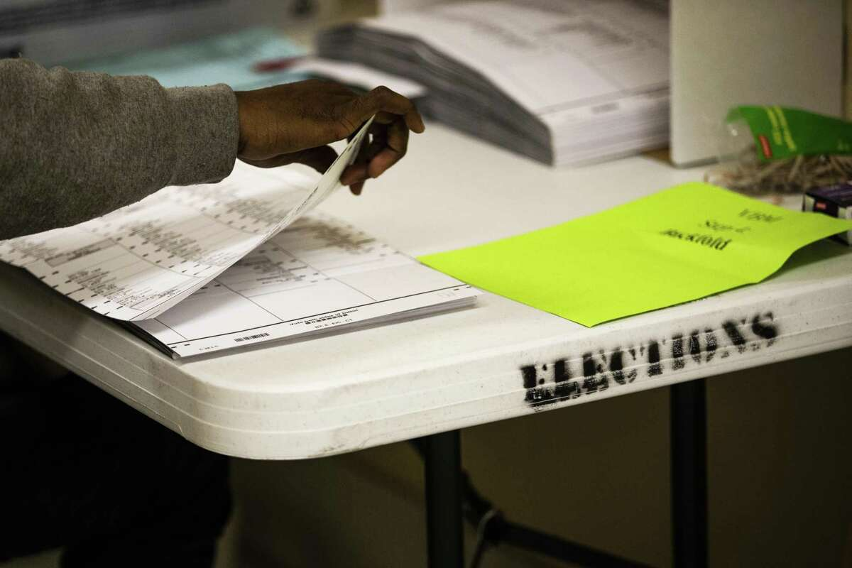 A worker unfolds and flattens ballots at the Department of Elections in San Francisco on Thursday.