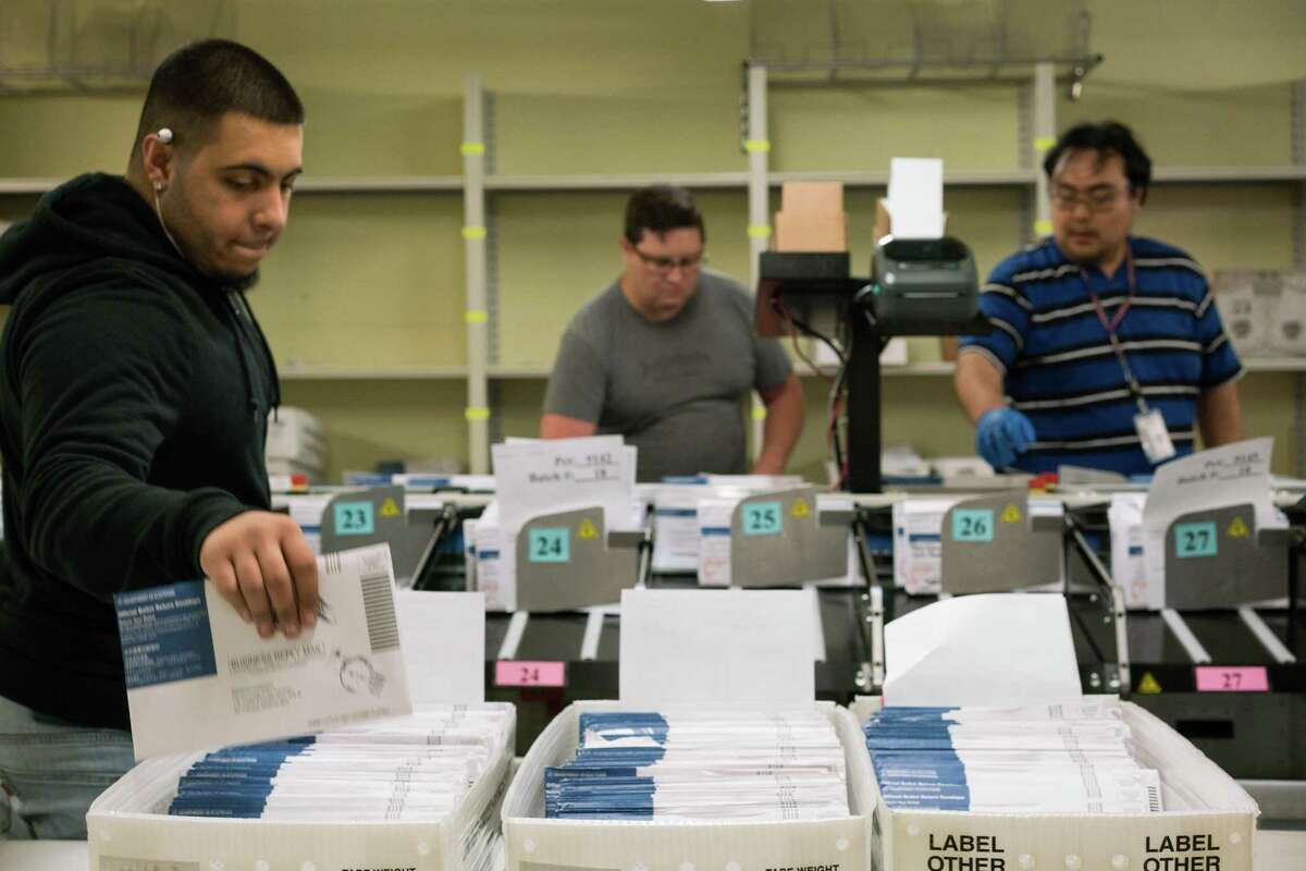 Damian Buoni (left), Zanzibar Tobogga and Joey Manalisay sort ballots at the Department of Elections in San Francisco on Friday.