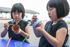 Twin sisters Laura(L) and Mary Chen of New Haven paint clay pots as part of the 18th annual Lead Awareness Picnic held Sunday at Lighthouse Point Park.