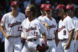South Carolina's LT Tolbert (11) celebrates with teammates after hitting a grand slam home run against Arkansas in the fifth inning of an NCAA college baseball tournament super regional baseball game in Fayetteville, Ark., Sunday, June 10, 2018. (AP Photo/Michael Woods)