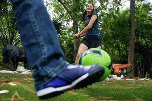 Mickie May Levin, 13, center, who collected more than 1000 cleats for her mitzvah project, Cleats for a Cause, kicks around a soccer ball with Jesus Vasquez, 10, outside her house  Monday, June 4, 2018 in Bellaire. Levin donated the cleats to underprivileged kids who want to play soccer.