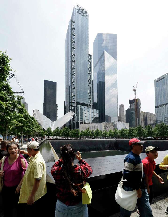 In this June 8, 2018 photo, 3 World Trade Center towers above visitors at the September 11 Memorial in New York. The center's latest skyscraper opens Monday. (AP Photo/Mark Lennihan) Photo: Mark Lennihan / Copyright 2018 The Associated Press. All rights reserved.
