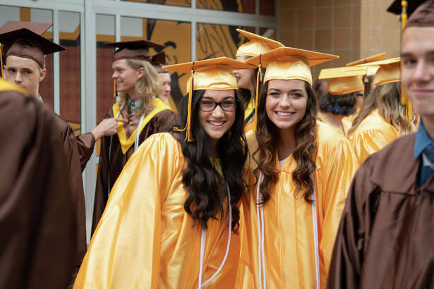 Makayla Goss and Amanda Hergenreder in the lineup at the  Bay City Western High School Commencement Sunday. (Steven Simpkins | for the Daily News)