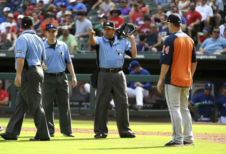 Home plate umpire Alfonso Marquez, center, signals for Houston Astros' George Springer to score after calling a balk on Texas Rangers relief pitcher Keone Kela as Astros manager AJ Hinch looks on during the ninth inning of a baseball game, Sunday, June 10, 2018, in Arlington, Texas. (AP Photo/Jeffrey McWhorter) Photo: Jeffrey McWhorter/Associated Press