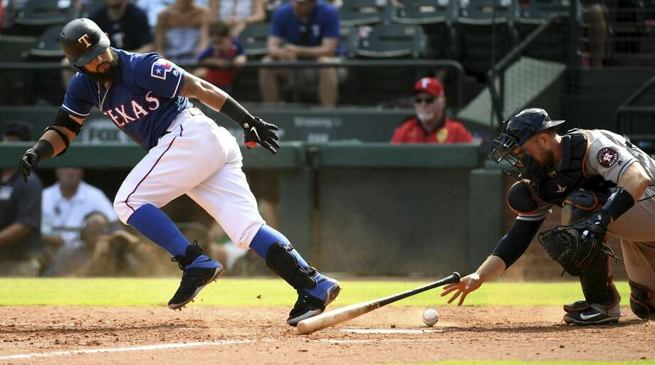 Texas Rangers' Rougned Odor, left, takes off for first base on a dropped third strike as Houston Astros catcher Max Stassi reaches to pick up the ball during the ninth inning of a baseball game, Sunday, June 10, 2018, in Arlington, Texas. Odor was thrown out on the play. (AP Photo/Jeffrey McWhorter) Photo: Jeffrey McWhorter/Associated Press
