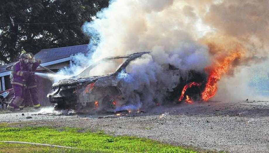 Virginia firefighters work to put out a car fire Saturday on Sugar Grove Road. The car was a loss, but no injuries were reported.