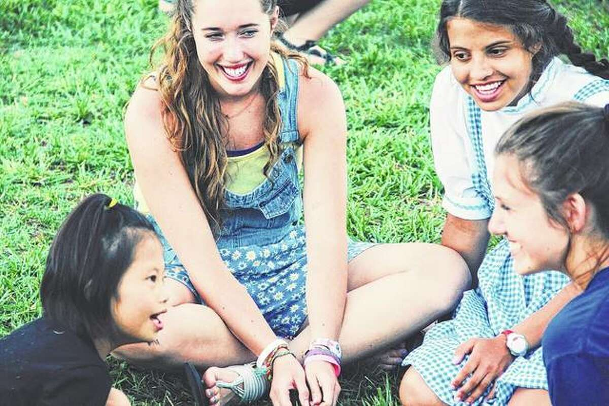 Anna Owens (second from left) and Alaina Coonrod (fourth from left), members of New Berlin Youth Group, talk with campers at Camp Barnabas, a Christian camp for people with special needs and chronic illnesses near Purdy, Missouri.