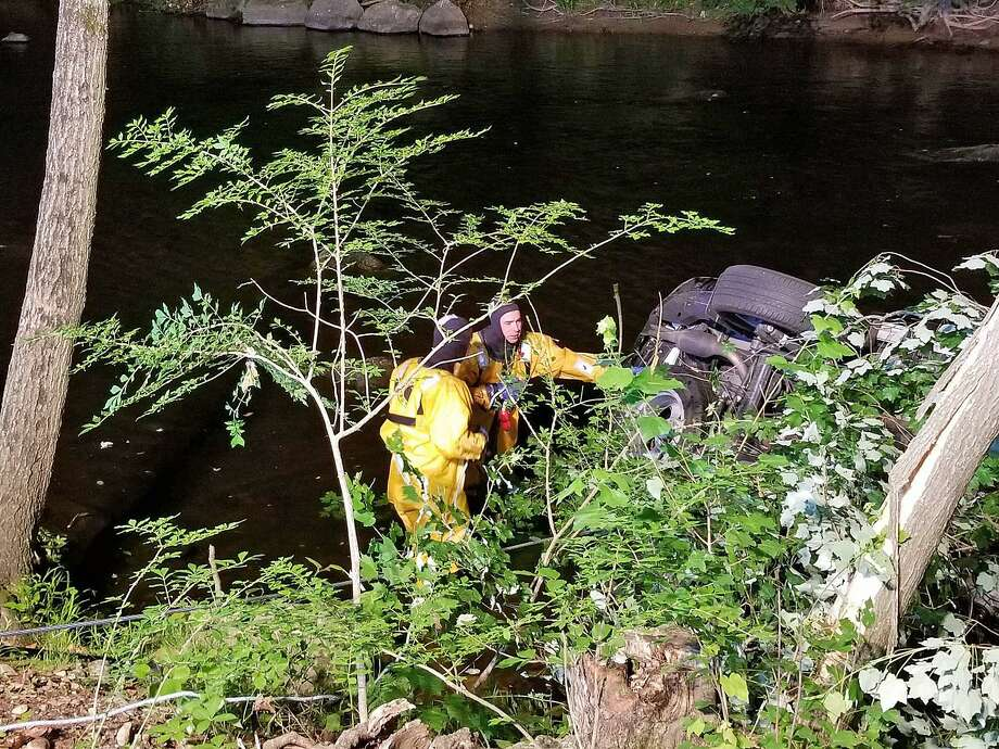 An SUV went off of Ford Road into the Saugatuck River on Sunday, June 10, 2018. The driver was able to get outside the vehicle and was uninjured. Two firefighters wearing cold water rescue suits entered the water and confirmed no additional occupants were in the vehicle. Photo: Westport Fire Department