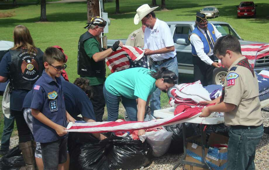 Scouts of Troop 845 and members of American Legion Post 629 work together to fold an estimated 130 flags at the flag retirement ceremony and demonstration held at Coldspring United Methodist Church on June 9. Photo: Jacob McAdams / HCN