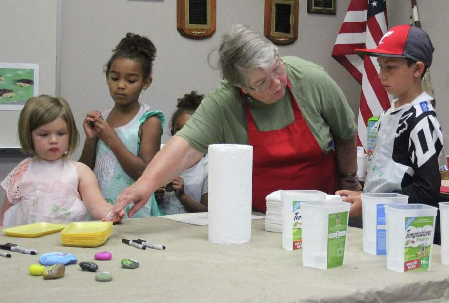 Karen Lee (second from right) teaches children at the June 6 Summer Reading program how to paint rocks at Coldspring Area Public Library. Photo: Jacob McAdams / HCN