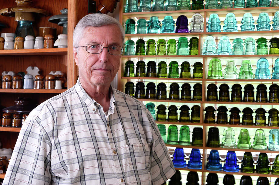 Elton Gish has collected glass and porcelain insulators since 1970, after first seeing a colorful glass insulator at a neighbor's house. His collection now occupies two rooms of his Lumberton home. 