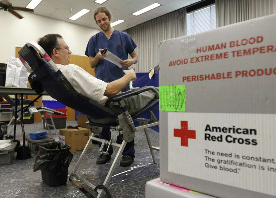 From left, state employee David Wainwright gives identifying information to American Red Cross phlebotomist Chris Culpepper on Wednesday, July 6, 2016. The Red Cross is launching its Missing Types campaign, which eliminates the letters A, B and O (also the three main blood types) from its branding to show how devastating it can be when blood types go missing from the blood supply. Harry Lynch/Raleigh News & Observer/TNS) Photo: Harry Lynch / TNS / Raleigh News & Observer