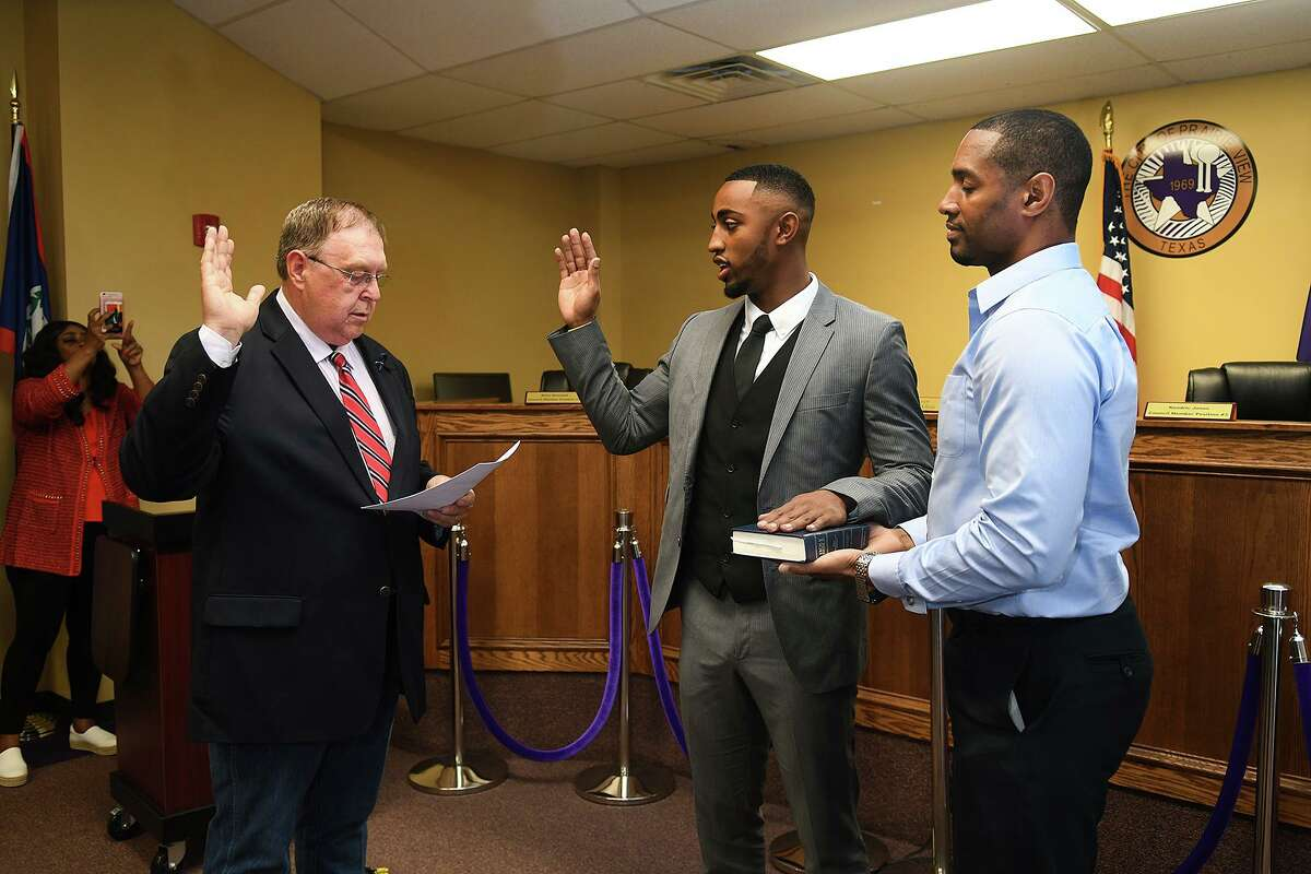 State Rep. Cecil Bell, from left, performs the swearing-in for new Prairie View Councilman Xante Wallace, 21, with Xante's dad Jeffrey holding the bible, at Prairie View City Hall on June 5, 2018.