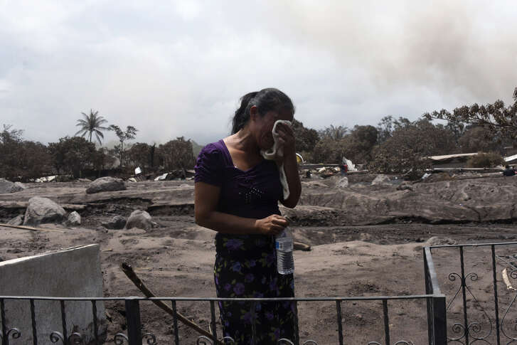 A woman cries while searching for relatives, victims of the Fuego Volcano eruption in the ash-covered village of San Miguel Los Lotes, in Escuintla department, about 35 km southwest of Guatemala City, on June 7, 2018. - The threat of fresh landslides forced emergency workers Thursday to suspend a search for victims of a major eruption of Guatemala's Fuego volcano, the country's disaster management agency said. To date, 99 people are known to have died in Sunday's major eruption of the volcano, with nearly 200 more still reported as missing. (Photo by JOHAN ORDONEZ / AFP) (Photo credit should read JOHAN ORDONEZ/AFP/Getty Images)