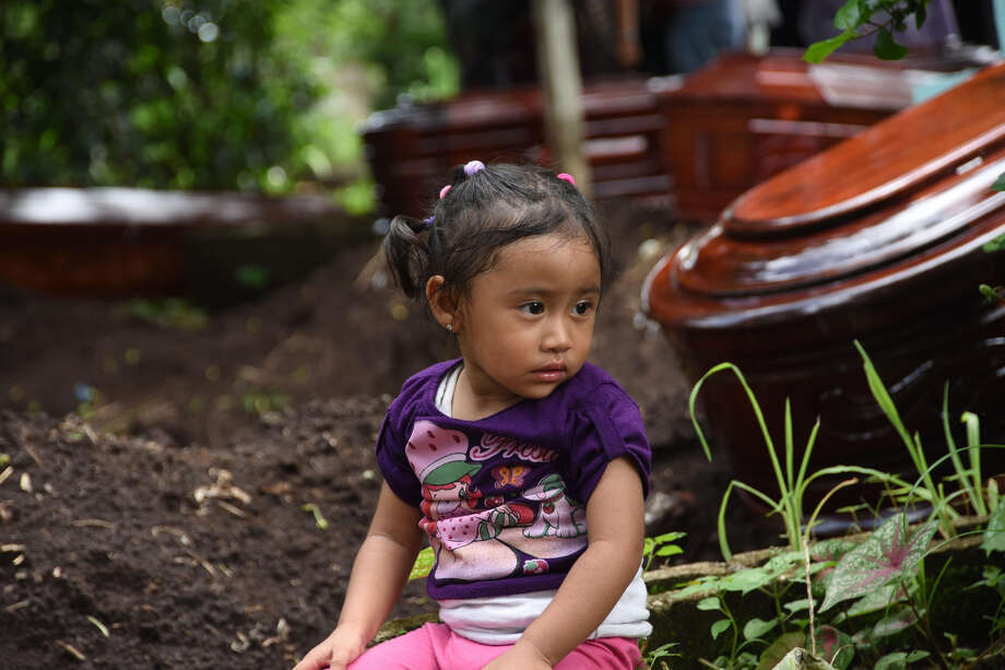 A girl sits near the coffins of five victims of the Fuego Volcano eruption outside Guatemala City. Photo: Orlando Estrada / AFP / Getty Images