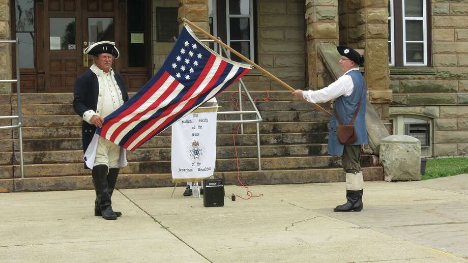 """John Stanton (left) and Jim DeGroff display the Serapis Flag. """"Flags tell our country's story,"""" said Genl. George Rogers Clark Sons of the American Revolution Chapter president Charles Dobias. """"Since shortly after our chapter's founding, we have been presenting a historic flag program each year on or around Flag Day, June 14th. This year's program was presented in front of the Greene County Courthouse in Carrollton on June 9th. The 50 state flags surrounded the property as historic flags lined the sidewalk to the building. Flag Day - the anniversary of the Flag Resolution of 1777 - was officially established by the Proclamation of President Woodrow Wilson on May 30th, 1916. While Flag Day was celebrated in various communities for years after Wilson's proclamation, it was not until August 3rd, 1949, that President Truman signed an Act of Congress designating June 14th of each year as National Flag Day. For more information about the SAR or to request a flag program, contact Rich Ruedin, 618-304-5135."""