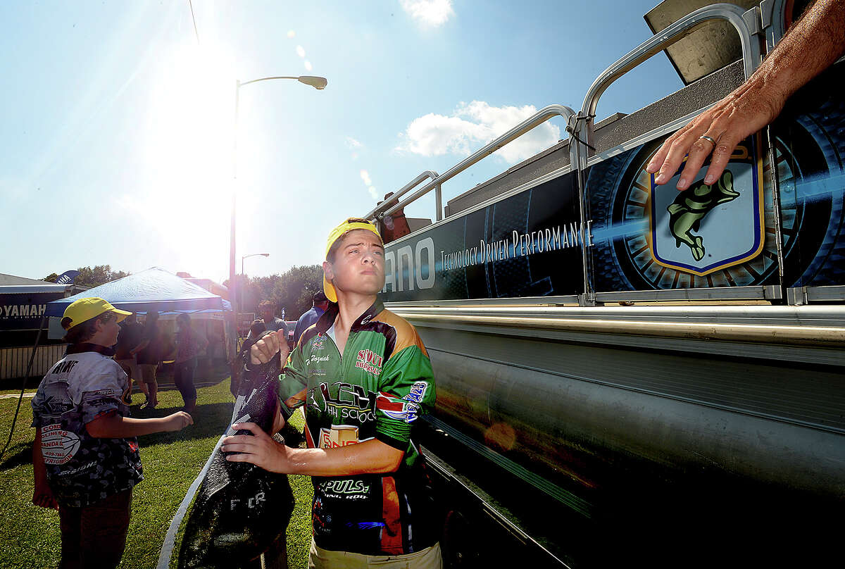 Little Cypress - Mauriceville fishing team member Wyatt Wozniak gets the next bag of anglers' catch after weigh-in while working at the live release station with contract tournament assistant Mike Macon as he and teammates volunteer behind the scenes at the Bassmaster Elite Series tournament in Orange. Photo taken Thursday, June 7, 2018 Kim Brent/The Enterprise